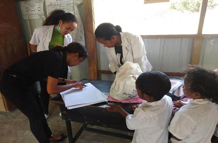 小学校での集団予防接種:台帳の付け方を指導するシェア職員